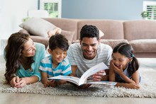 Mixed Race Parents And Children Lying On Rug Reading Book