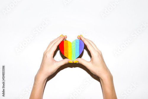 Painted heart shaped lgbt flag in hands on white