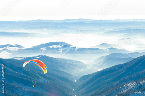 Deurstickers Luchtsport Paragliders launched into air from the very top of a snowy slope of a mountain