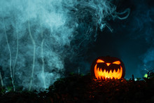 Spooky Gleaming Jack-o-Lantern In Dark, Smoky Setting With Copy