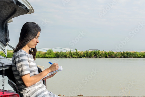 Fototapety, obrazy: young woman sitting on hatchback and drawing in notebook
