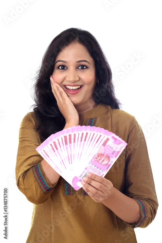 Poster Happy young woman holding Indian 2000 rupee notes