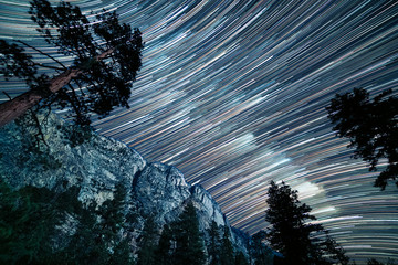 FototapetaLong star trails of the milky way pass over the top of Kern canyon in a long exposure showing the granite cliffs and pine trees