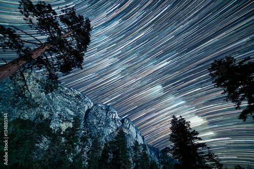 Photo  Long star trails of the milky way pass over the top of Kern canyon in a long exp