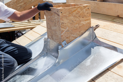 Fotografía  Roofer builder worker attach metal sheet to the chimney