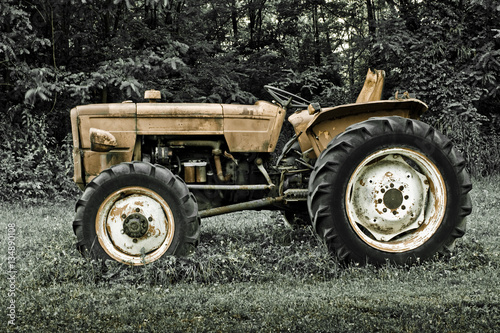 Fototapety, obrazy: Rusty tractor abandoned in a field