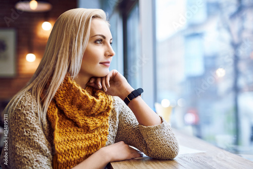 Fotomural  thoughtful young woman looking through  window in a cafe during