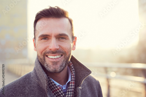 Photographie Portrait of happy man smiling outdoors during cold winter day