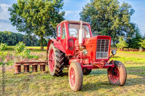 Photo  Landwirtschaftliches Fahrzeug - alter Traktor auf einem Feld stehend