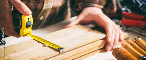 Fotografering Carpenter holding a measure tape