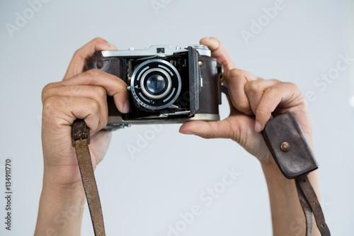 Fototapeta Close-up of female photographer holding old fashioned camera obraz na płótnie