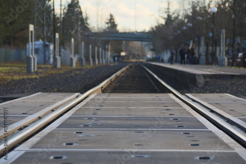 Close Up of Railroad Tracks/Crossing with Passengers, Platform, Trees in Blurred Canvas Print