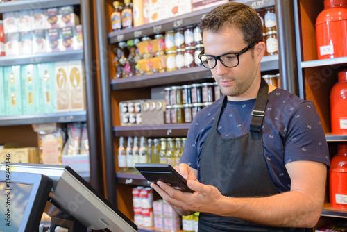 Shop keeper using calculator Fototapete