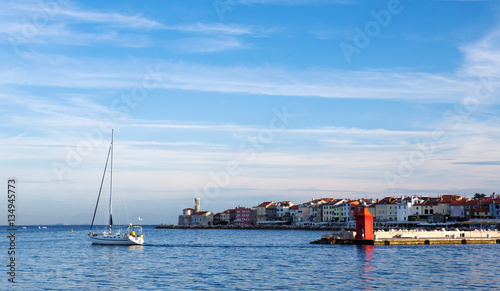 City on the water Quay Slovenian town of Piran at dawn, a small sailboat and lighthouse in the sea.