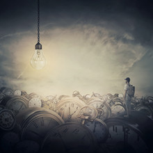 Time Trash. Surreal View As A Man, With A Bag In His Back, Stand In The Midle Of A Clock Trash Looking At A Huge Light Bulb Glowing. Time Pressure, Hour Perception And Idea Concept.