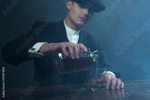 Fotografiet  Retro 1920s english gangster with flat cap pouring whiskey. Peak