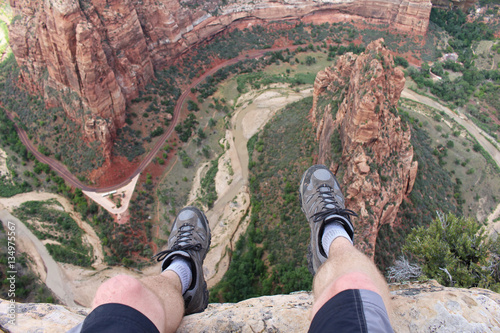 Obraz na plátne First person perspective shot from a hiker sitting at the edge of a cliff at Angel's Landing in Zion National Park