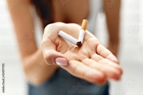 Fotografia Woman Hand Showing Broken Cigarette. Unhealthy Lifestyle