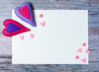 Hand made felt hearts decorations white paper on wooden background
