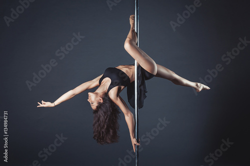 Young slim pole dance girl of asian appearаnce on a black studio background