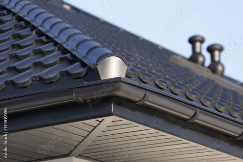 Fototapeta Corner of the new modern house with gutter and ventilation chimneys. obraz