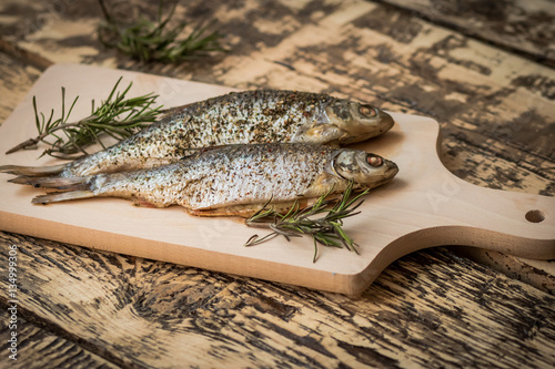 oven-baked fish on the cutting board with a sprig of rosemary