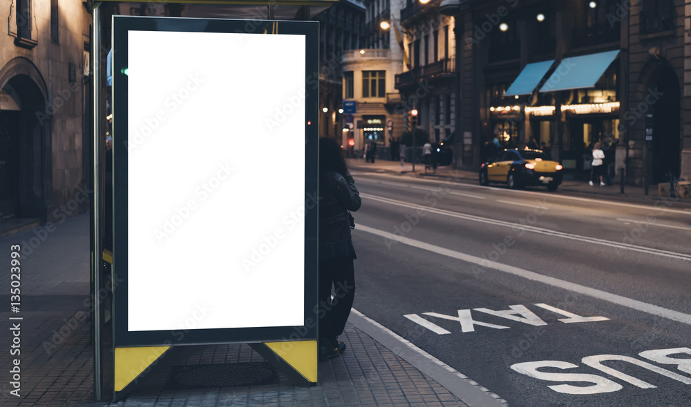 Fototapeta Blank advertising light box on bus stop, mockup of empty ad billboard on night bus station, template banner on background city street for poster or sign, afisha board and headlights of taxi cars.