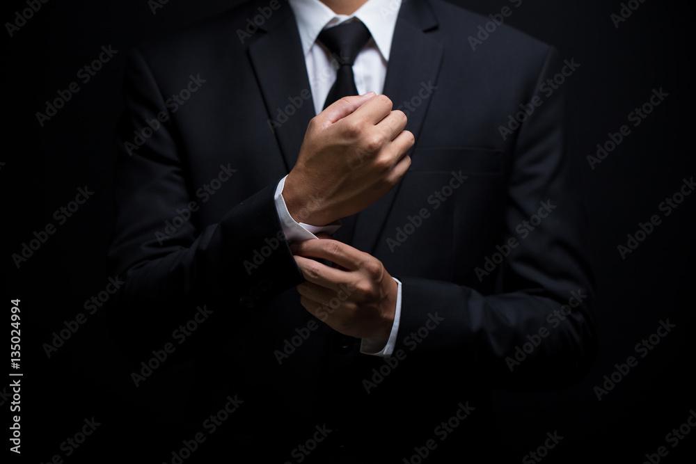 Fototapeta Businessman adjusting his cufflinks