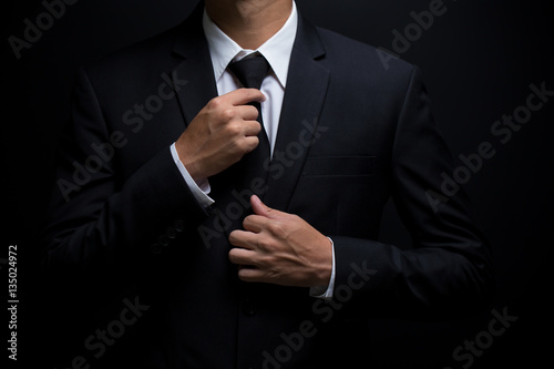 Fotografie, Obraz  Man in black suit and adjusting his necktie