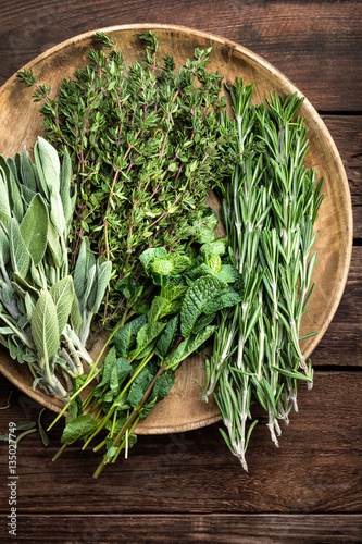 Photo various fresh herbs, rosemary, thyme, mint and sage on wooden background
