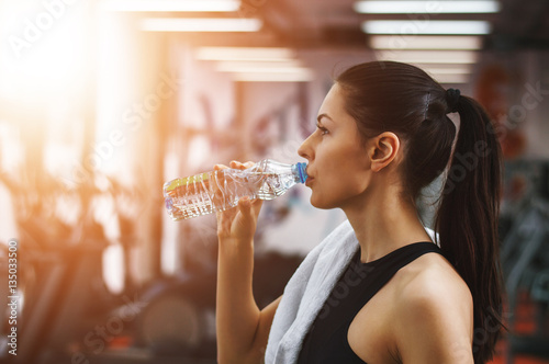 Foto op Plexiglas Fitness Refreshing after workout. Beautiful young woman in sports clothi