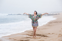 Portrait Of A Happy Mature Woman With Outspread Arms Enjoying Freedom On The Ocean Beach. Freedom Of Travel Vacation. Wellness And Happiness Lifestyle Concept. Portugal. Santa Cruz