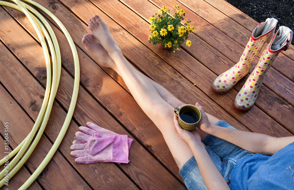 Fototapety, obrazy: Woman with cup of coffee sitting on a patio wooden deck resting after working in the garden