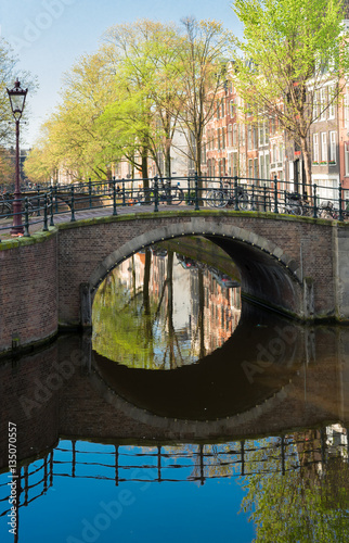 Photo  View of historical bridge over canal with mirror reflections in water, Amstardam