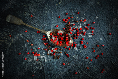 Printed kitchen splashbacks Black, red peppercorns mixed with salt on old rustic spoon. dark blue stone background.