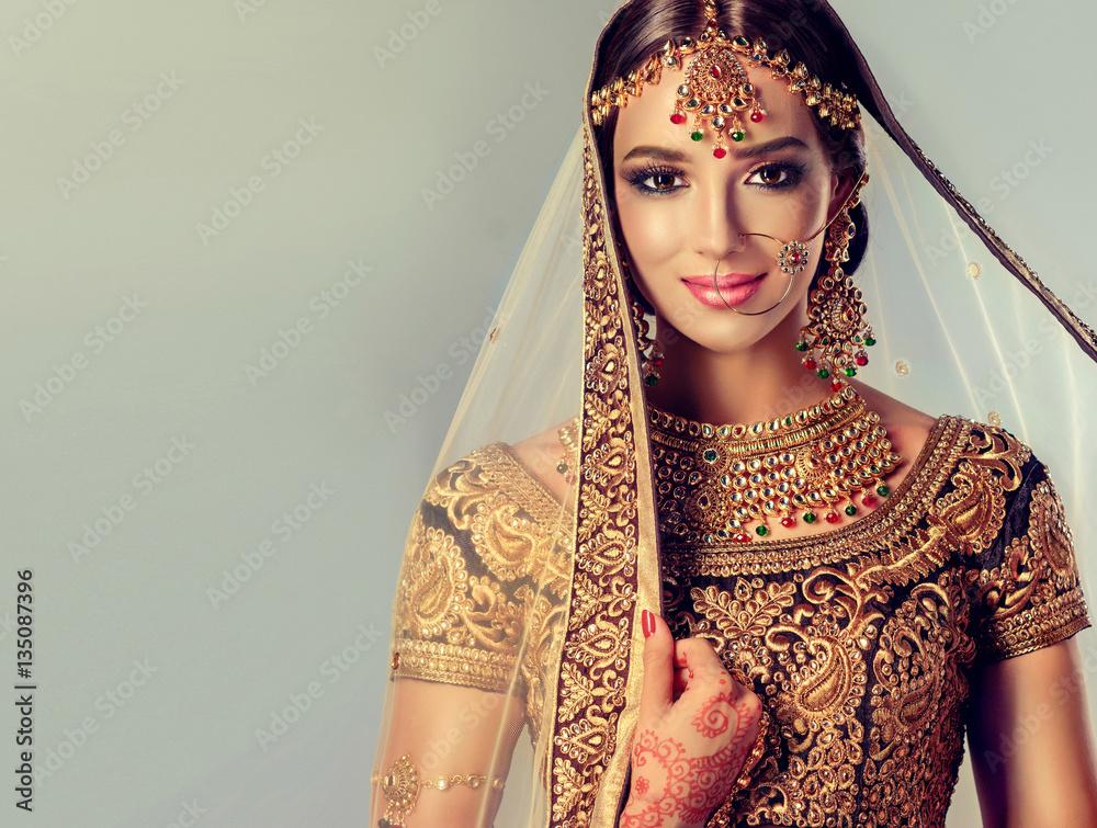 Fototapeta Portrait of beautiful indian girl. Young hindu woman model with golden kundan jewelry set . Traditional Indian costume lehenga choli .