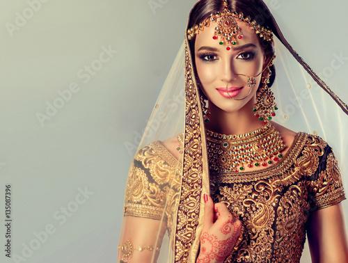 Portrait of beautiful indian girl. Young hindu woman model with golden kundan jewelry set . Traditional Indian costume lehenga choli .  Wall mural