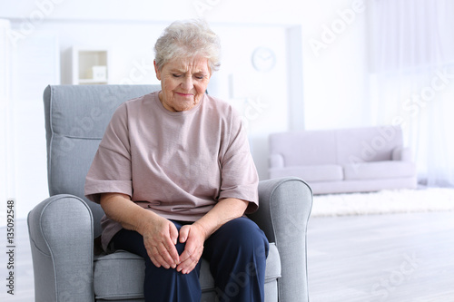 Fotografiet  Elderly woman suffering from pain in knee at home