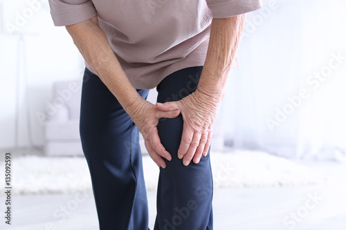 Fotografiet  Elderly woman suffering from pain in knee at home, closeup