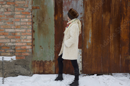 Poster Havana The young beautiful girl with dark hair in a bright sheepskin coat on a background of a winter landscape