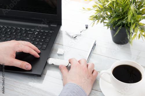Fotografia Man plugging GSM modem into a laptop
