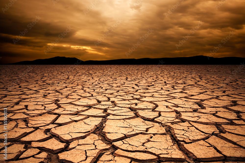 Fototapeta dramatic sunset over cracked earth. Desert landscape background.