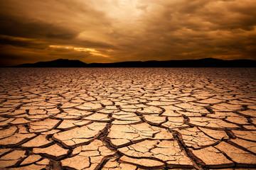 dramatic sunset over cracked earth. Desert landscape background.
