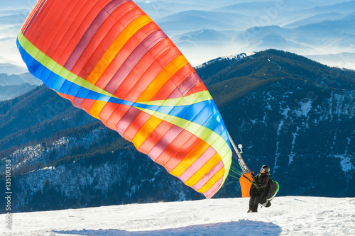 Fotobehang Luchtsport Paraglider launching into air from the very top of a snowy mountain slope