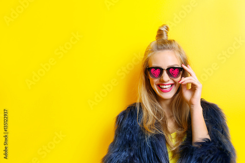 Young beautiful woman wearing sunglasses with hearts on yellow background