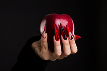 Hands With Scary Nails Manicure Holding  Poisoned Red Apple , Isolated On Black Background