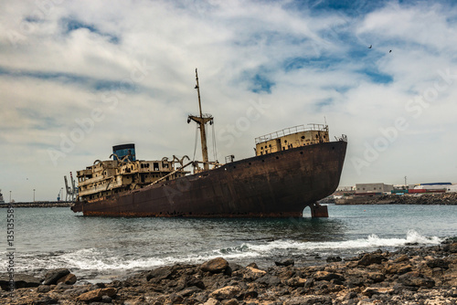 Photo Stands Shipwreck Rusty Spanish ship in the waters near Lanzarote