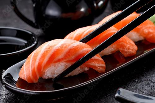 Printed kitchen splashbacks Sushi bar Japanese cuisine. Salmon sushi nigiri on a black plate with chopsticks.