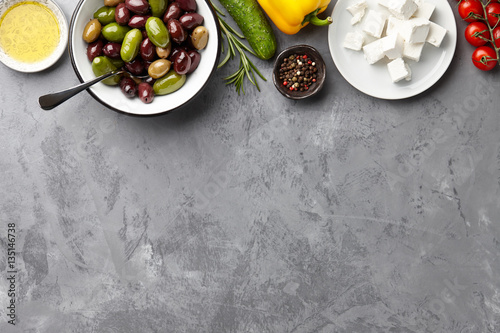 Fototapeta Greek salad main ingredients: fresh olives mix, feta cheese, tomatoes, pepper, cucumbers and olive oil garnished with rosemary on stone background obraz