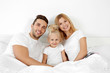 Cute happy family lying in bed at home
